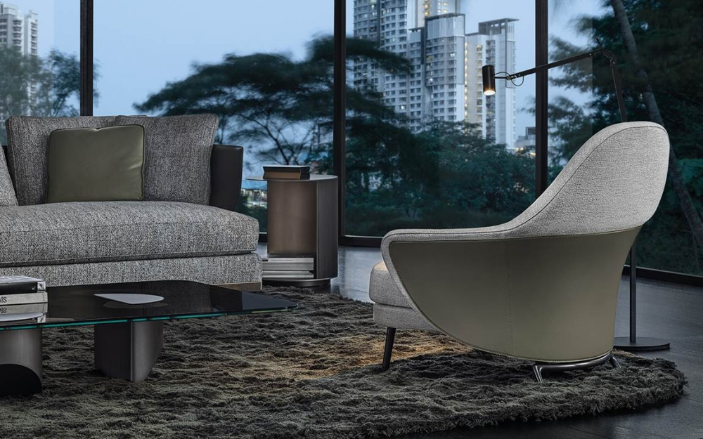 ANGIE ARMCHAIR by GAMFRATESI STUDIO, designed in 2019. A saddle hide element designs a wing that embraces the armchair, sustaining the frame like a sculptural bustier characterized inside by the inviting softness. Behind the apparent simplicity of the design lies an advanced technological process used to make both the padding with different textures of foam and the saddle hide bustier, made using two different BAYDUR® moulds, which perfectly follows the curved line of the armchair and available in bordeaux, ash, dove grey, sage, mud, mocha and black colours.