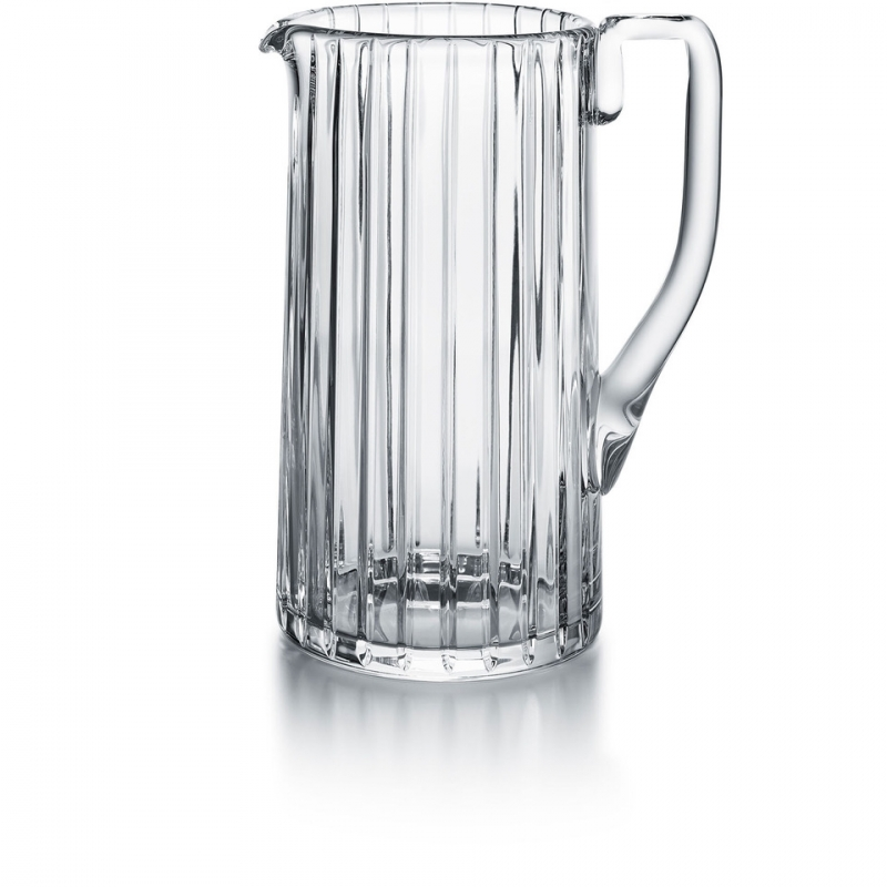 Baccarat HARMONIE pitche. Parallel vertical lines travel cleanly along the silhouette finely grazing the clear crystal form from the lip to the base. This linear emphasis evokes a thick clear crystal column.The stripes are subtly yet precisely etched into the clear crystal surface, showcasing the three-dimensionality of the pitcher and creating a visual depth to the liquid within. The vertical sweep of the striping is present throughout the HARMONIE collection, which includes highballs and tumblers and other pieces to complete a well-stocked bar. The HARMONIE pitcher is a stunning item that makes having a drink all the more enjoyable.