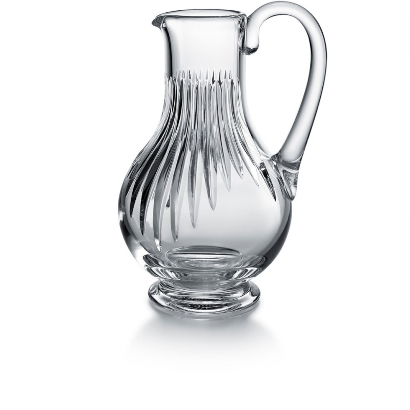 Baccarat MASSÉNA pitcher. Deep orgue bevel cuts are etched directly into the clear crystal, irradiating along the ample rounded globe towards the base. Their intricacy, in turn, put the smoothness and lucidity of the upper bowl into sharp relief. The stunning silhouette and prismatic optical effects of the cuts make the MASSENA pitcher a great addition to any table, one that accents any festive occasion or special soirée with a luminous beauty and optical splendor. The pitcher is just one element of Baccarat's iconic MASSENA bar and tableware collection, which encompasses wine glasses, highball glasses, and tumblers. All pieces from the MASSENA collection share scrupulously rendered orgue bevel cuts.