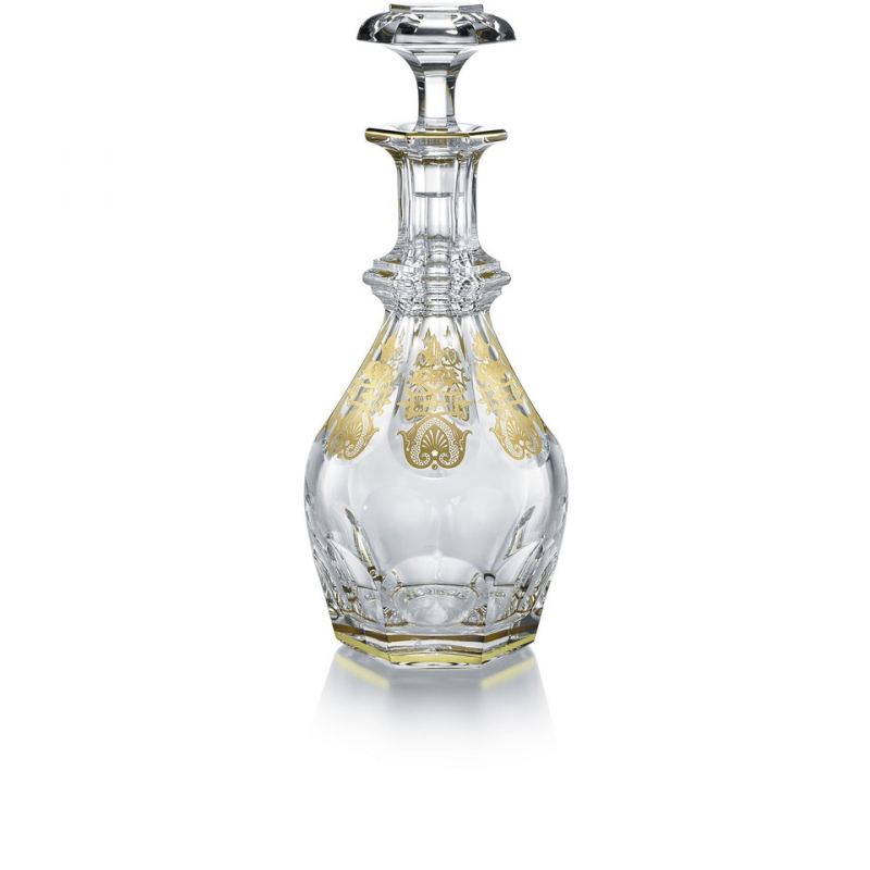 The HARCOURT EMPIRE decanter revisits the HARCOURT's regal architectural form. The HARCOURT collection, created in 1841, is the oldest in the Baccarat archive and reputed for its iconic design. The HARCOURT EMPIRE decanter shares the same structure as the HARCOURT 1841 square whiskey decanter, but adorned with exquisite golden embellishment. Each flat cut side has gilded decorative shapes applied with a light hand, and a gold trim around the perimeter of both the decnater's neck and base. The diamond-cut beveled stopper crowns the classical shape with geometric sophistication. The HARCOURT EMPIRE collection, a showcase of sparkling lucid crystal complemented by graceful gold, also includes a wine glass, highball glass, and champagne flute. Baccarat's Rivoli stemware collection has gilded features as well.