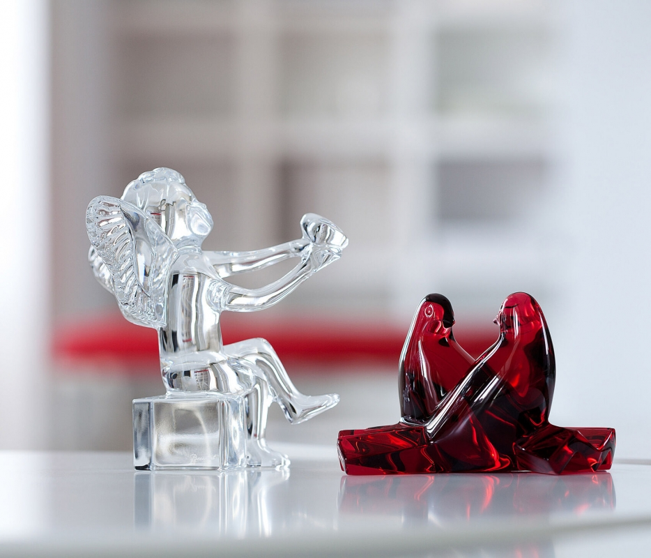 ANGE CHERUB designed by JEAN-PIERRE GODON. Gracefully seated with criss-crossed legs and extended arms, this wholesome cherub willingly offers his heart to the person he adores. The cherub's face is titled upwards, cementing the connection between himself and his loved one with this declarative gesture. Designed by JEAN-PIERRE GODON for Baccarat, this little cupid is a wonderfully tender-hearted emblem of devotion. Be it to celebrate Valentine's Day or honor an anniversary, this angel figurine is suitable for any sentimental occasion that warrants a beautiful token of affection for your beloved. Price €270