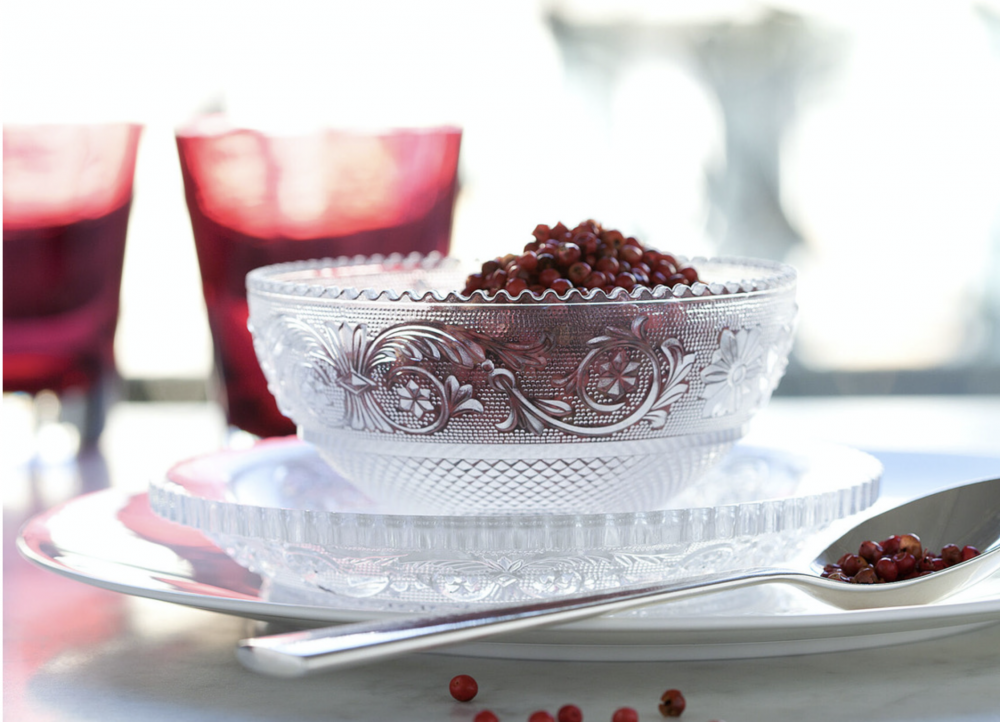 The  Clear crystal ARABESQUE dessert plate has a great variety of detailing, which accentuates Baccarat's striking artistry and savoir-faire. The scalloped edges rise and fall in tiny waves.  Just below, a thick belt of geometric swirls —a motif embellished with stars and acanthus leaves—wreathes around the plate. This intricate garland is hemmed in by the Clear crystal crosshatching that decorates the underside of the dessert plate. Created for Baccarat in the 19th century, this model originally encompassed a complete table set (with jug, decanter, goblets and various stemmed glasses). Today, the ARABESQUE collection has been pared down to the dessert plates and bowl, both of which share incredible and elaborate detailing. Price from  €65 to €165.