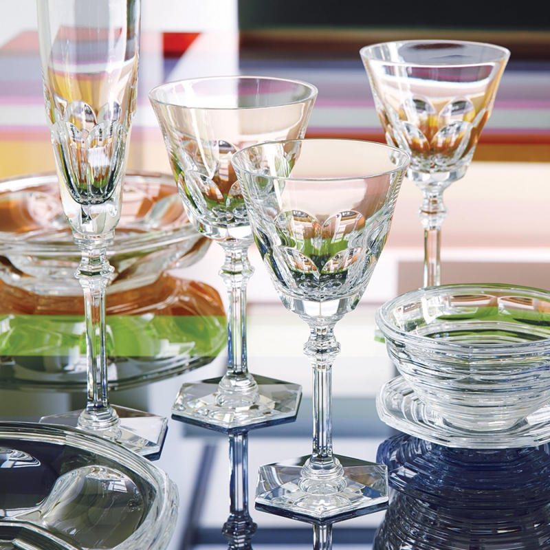 """HARCOURT EVE glass. In 2013 the HARCOURT glass reinvents its distinguishing features and is renamed """"EVE"""". Perched on its emblematic hexagonal foot, with its graceful, lean silhouette, this new, taller and finer glass asserts its femininity and is available as a champagne glass, wine glass and water glass. This set is sure to become a new classic and offers 3 glass sizes as well as a champagne glass."""