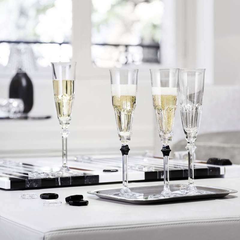 HARCOURT EVE champagne glasses. Adorned with a black button, the EVE champagne glasses gives a touch of daring and perfect elegance to your table in a subtle play of contrasts between light and shadow