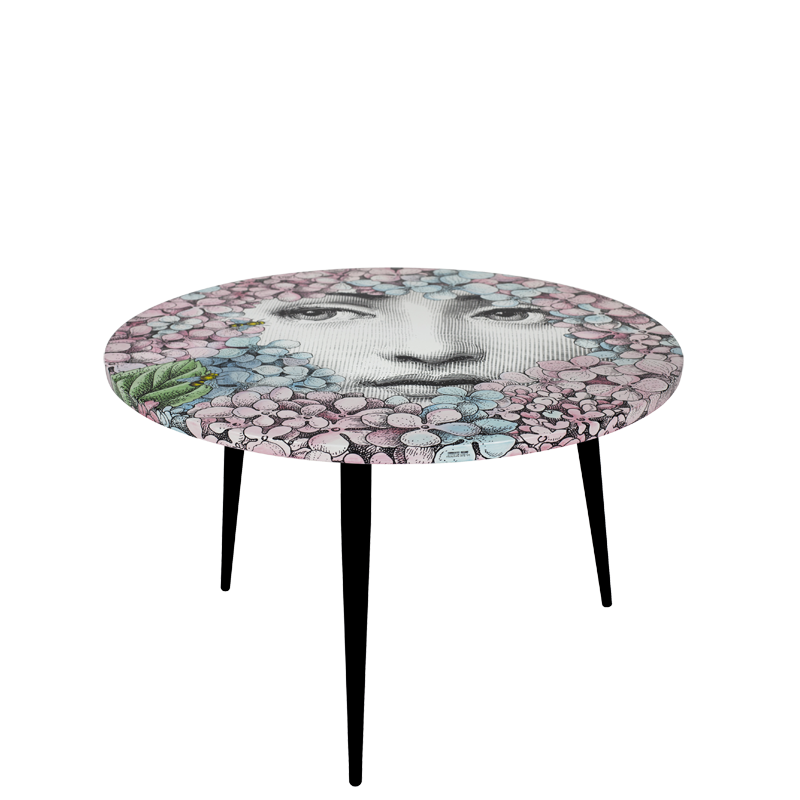 TABLE ORTENSIA. THE ROUND TABLE IS DRESSED WITH THE DÉCOR ORTENSIA (HYDRANGEA), A RECENT REINVENTION BY BARNABAFORNASETTI. THIS MOTIF ENRICHES THE SERIES TEMA E VARIAZION (THEME AND VARIATIONS) WITH A REINTERPRETATION OF LINA CAVALIERI ICONIC FACE PEEKING AT THE OBSERVERS BEHIND COLOURFUL AND JOYFUL HYDRAGEAS, THE SAME PLANTS THAT HAVE SURROUNDED CASA FORNASETTI IN MILAN FOR 60 YEARS. THE TABLE IS PRINTED, LACQUERED AND PAINTED BY HAND.