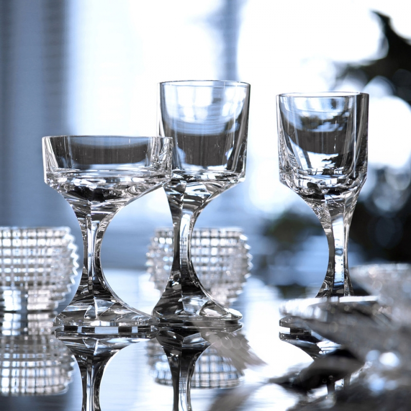 NARCISSE glass. A sculptor and furniture designer, BORIS TABACOFF imagined the NARCISSE set back in 1971. In gift-set of two glasses, the NARCISSE glasses add a sublime touch to the most original dinner table with its timeless design. An asymmetrical and distinctly avant-garde creation embracing the quest for new shapes. In the image of the narcissus, whose flowers bend and lean towards water, the off-center glass bowl seems to bow. The perfect balance is obtained thanks to the talent of the manufactory's artisans.