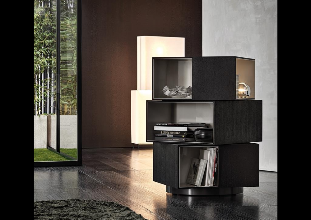 PAGE by RODOLFO DORDONI, designed in 2019. With its decidedly sculptural presence and the contrasting textures of the interiors and exteriors of its three volumes, the page bookcase is inspired by works of modern art. Its misaligned blocks, set one on top of the other also call to mind contemporary architectures. Fully swivelling, it is characterised by volumes in the form of parallelepipeds, with outer edges in mocha-coloured wenge wood and glossy painted warm grey-coloured interiors, and it stands on a circular base with a glossy pewter-coloured finish. A bold piece of furniture that is sure to turn heads, ideal in any part of the room, including the centre. In addition to its function as a bookcase, page can also be used as a contemporary display cabinet to accommodate objects or as a bar cabinet.