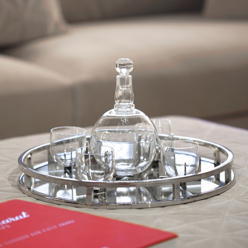 Baccarat - heritage PARAISON set. Baccarat presents an original re-issue of the PARAISON set created in 1931 by GEORGES CHEVALIER in the modernist mood of the Art Deco years. The set is composed of four glasses and a decanter. Crafted with amazing finesse, the set is a genuine masterpiece of expertise. The avant-garde design, combining the glitter of crystal with the austerity of metal, embodies the genius of GEORGES CHEVALIER, who took Baccarat into the modern era. The Maharajah of Indore, famous for his sumptuous orders placed with the leading names in luxury and his exquisitely fine taste, acquired this set in 1933 for his magnificent Art Deco-style Manik Bagh Palace. The timeless PARAISON set has retained its minimalist lines to glamorously highlight all occasions now and for years to come. This box holds a whiskey bottle and 4 PARAISON Héritage tumblers.