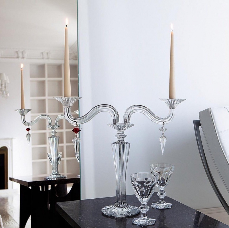 MILLE-NUITS candelabra. The bevel-cut arms of the candelabra, amidst which stand two decorative crystal swirls, glitter luminously. Each candelabra arm is adorned with dangling arrowhead-shaped crystals that catch the light in a scintillating manner. Candles nestle within crystal candleholders shaped like blooming daffodils. The MILLE NUITS candelabra is a sumptuous item, made in two-, three-, or five-light versions; also available in gold. Hurricane shades, available separately, emphasize every candle flicker and intensify the luminosity. Designed for Baccarat by MATHIAS, MILLE NUITS is a reference to the 1001 Tales of The Arabian Nights. The MILLE NUITS collection also encompasses chandeliers, stemware, and home décor. Price from €2,700 to €7,800