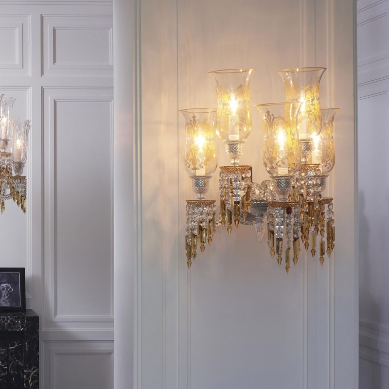 """ZÉNITH wall sconce CHARLESTON. Chandeliers, floor candelabra and sconces are adorned with """"champagne draped-prisms"""" reminding us long pearl necklaces, draped dresses of Charleston dancers. This collection also pays tribute to the creations of Georges Chevalier, his boldness and genius in particular through Jets d'eau collection. The latter is also in the history of the Maison Baccarat and its private mansion. Indeed, Marie-Laure de Noailles, the owner of this place during this period, was actively involved in the expansion of this movement conducive to creativity, art and renewal. In this spirit the Charleston chandelier has been chosen to adorn the first Baccarat Hotel in New York. The color is a main element in the creation of this new collection."""